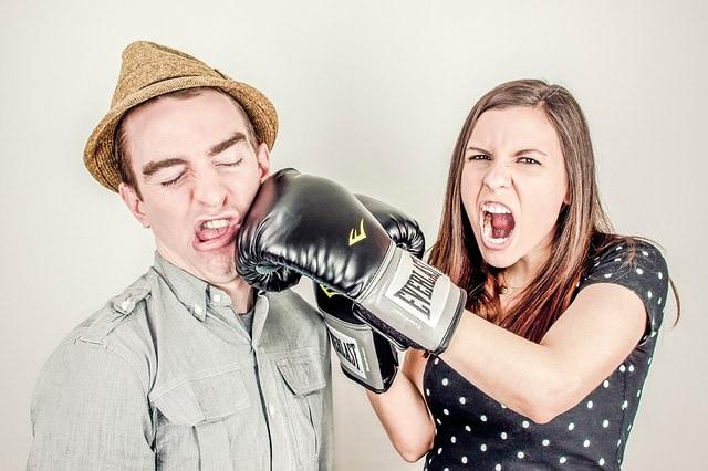 Junge Frau mit Boxhandschuhen, gibt Mann Kinnhaken