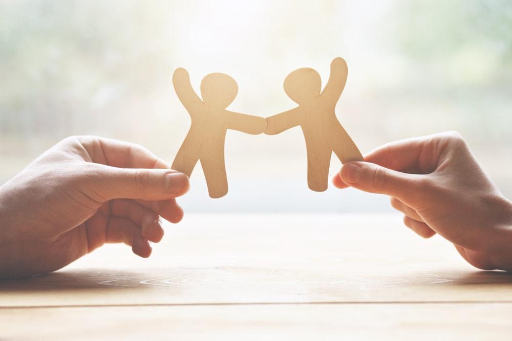 Zwei Hände eines Paares, die zwei Holzfiguren Mann und Frau in der Hand halten